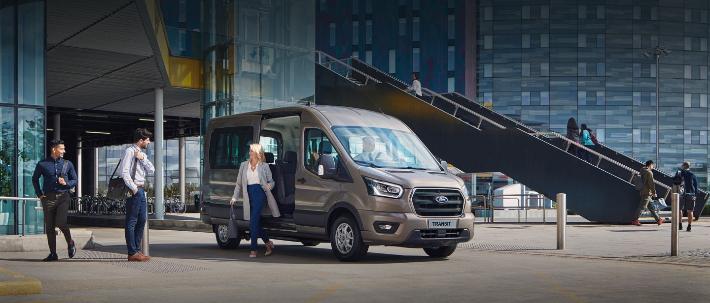 All New Ford Transit Minibus parked outside glass building